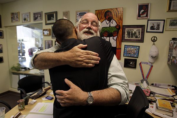 In a Friday, June 4, 2010 photo, Father Gregory Boyle hugs Robert Trejo, a former gang member, in his office at Homeboy Industries in Los Angeles. Organizations trying to prevent youngsters from joining gangs have been hit hard by the sour economy. Homeboy Industries, which employed ex-gang members as a way of keeping them off the street, had to fire more than 300 of its workers as donations and city subsidies plummeted. (AP Photo/Jae C. Hong)